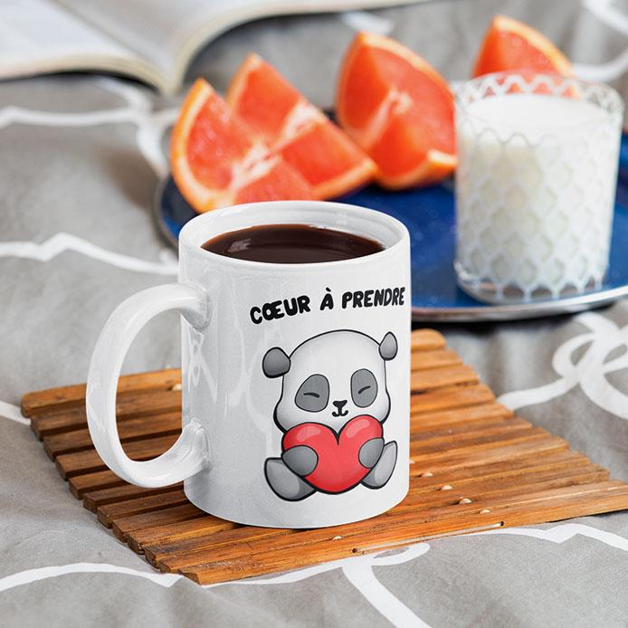 Un mug de panda qui tient un coeur rouge