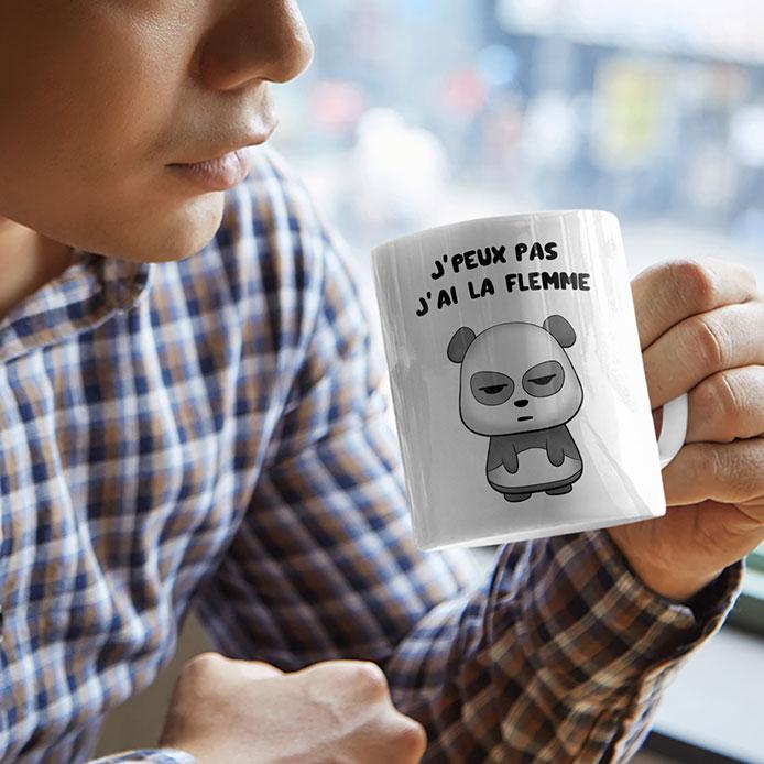 Un homme qui tient une tasse avec un panda illustré.